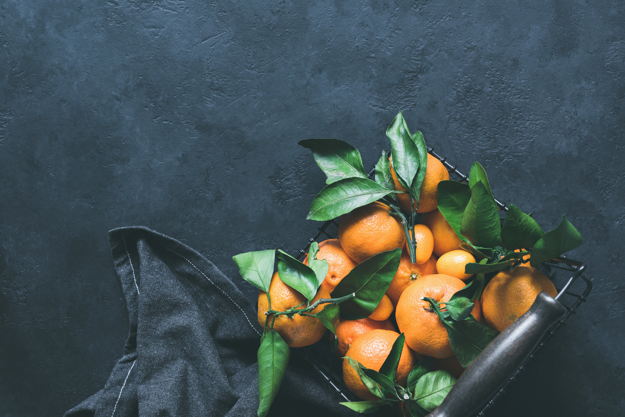 Mandarines or tangerines with leaves in basket on concrete background. Top view, copy space for text