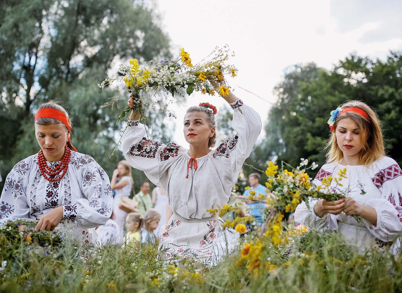Women make wreaths during a celebration on the traditional Ivana Kupala (Ivan the Bather) holiday, the ancient tradition, originating from pagan times, is usually marked with grand overnight festivities during which people sing and dance around campfires, believing it will purge them of their sins and make them healthier, in Kiev, Ukraine, July 6, 2016.  REUTERS/Gleb Garanich - S1AETOBXEPAA