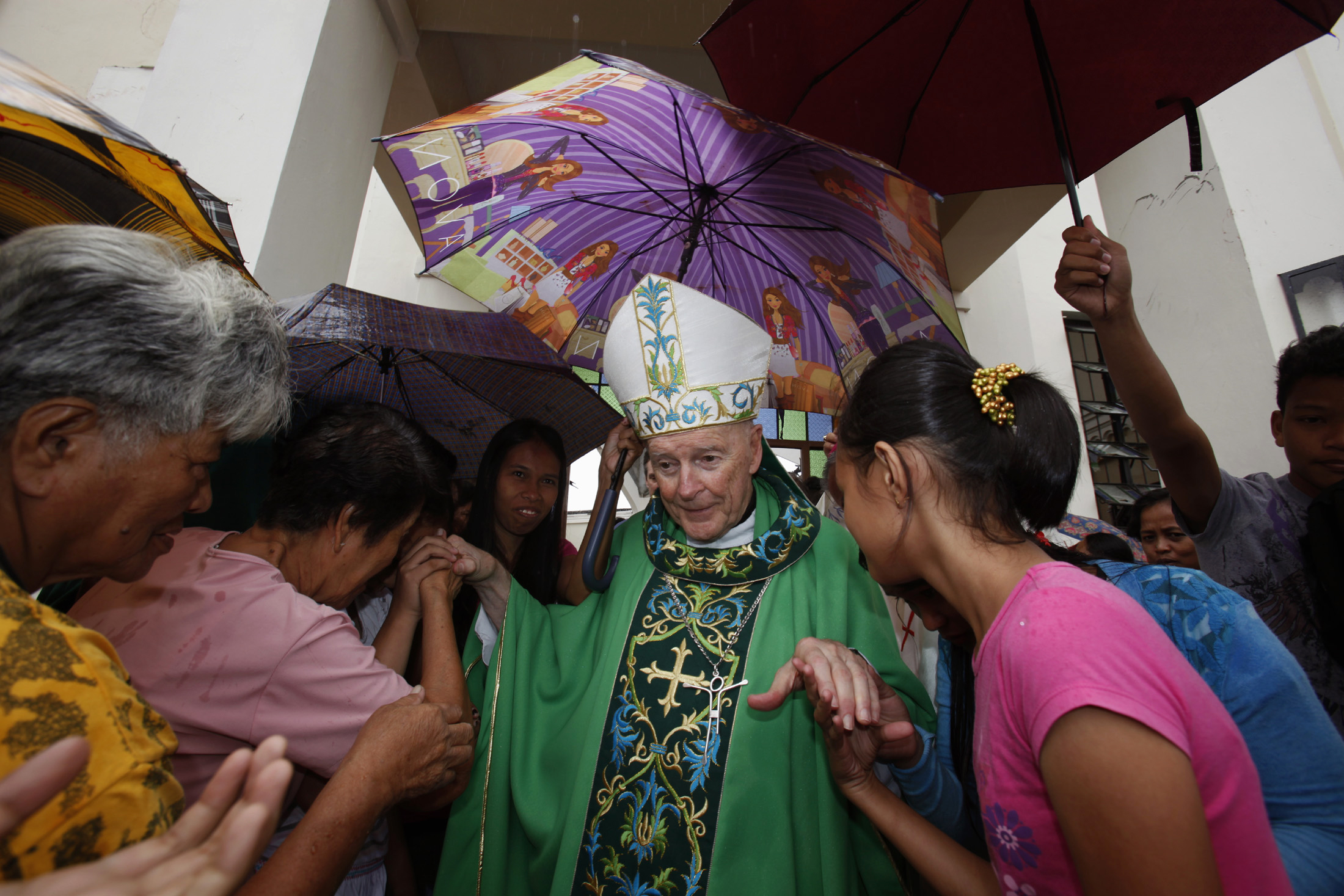 People greet Cardinal Theodore E. McCarrick, President of the Catholic Relief Services based in Washington, outside Transfiguration Cathedral, which was damaged during super Typhoon Haiyan, in Palo, south of Tacloban, November 17, 2013. Long-delayed emergency supplies flowed into the typhoon-ravaged central Philippines on Saturday, reaching desperate families who had to fend for themselves for days, as the United Nations more than doubled its estimate of homeless to nearly two million.   REUTERS/Bobby Yip (PHILIPPINES  - Tags: DISASTER RELIGION ENVIRONMENT)   - LR1E9BH0AF5BZ