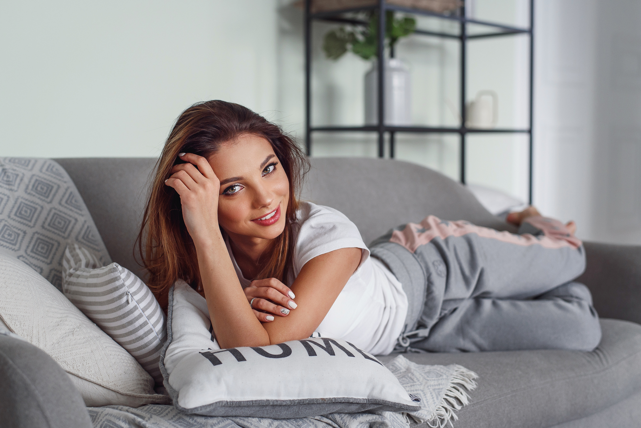 A pretty young woman with beautiful smile lies on grey couch with pillows at cozy home. Cute girl having rest at home in lazy day.