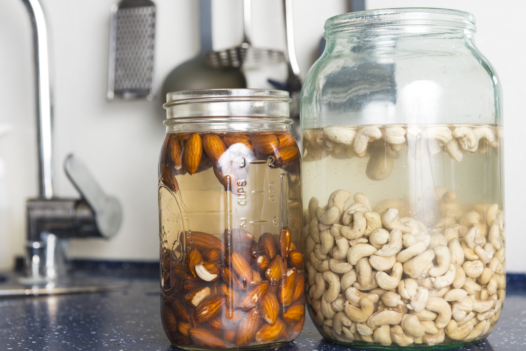 Soaked almonds and cashews in large glass in domestic kitchen. They are used to prepaire raw vegan cheese and other raw recepies.