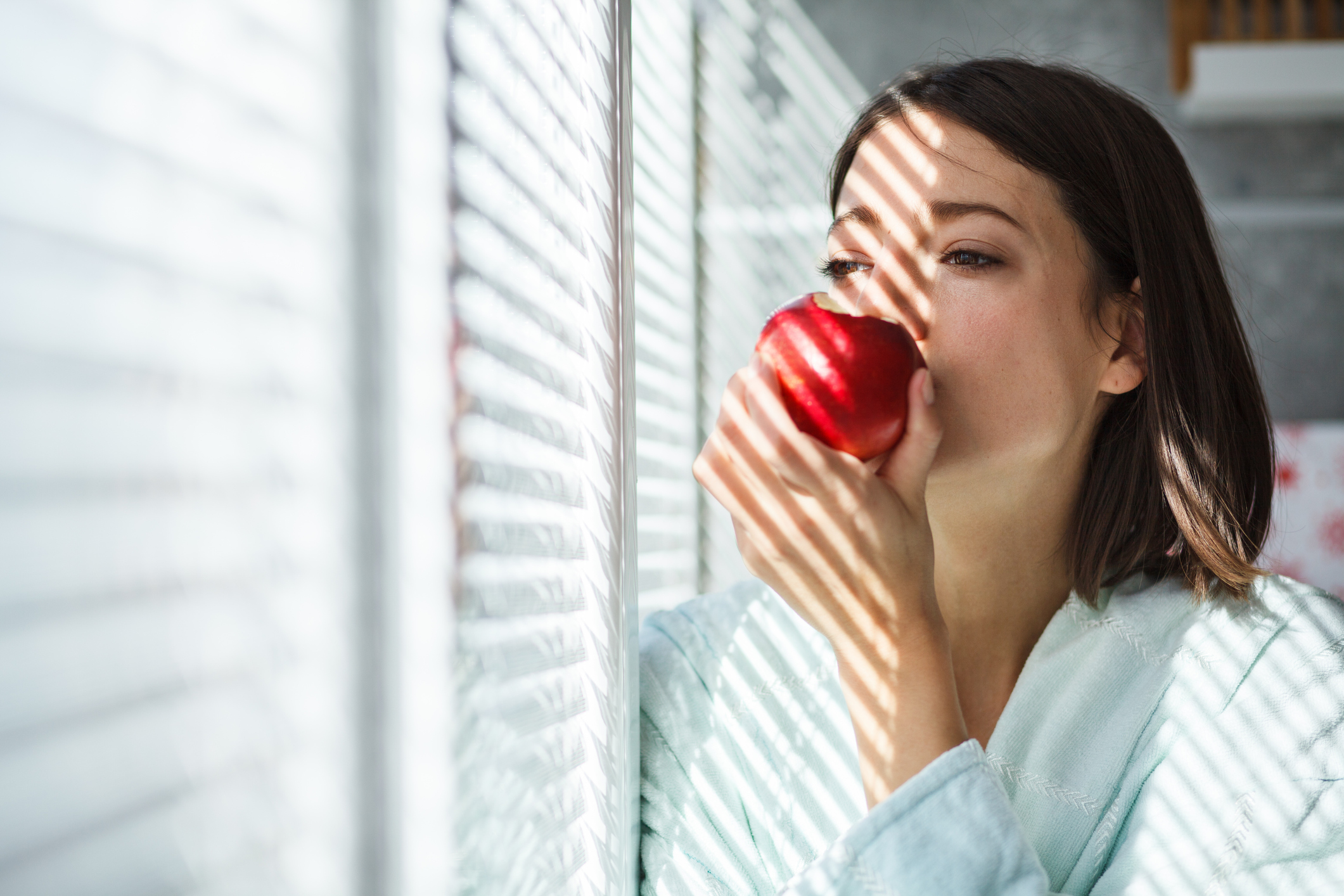 Copy space shot of a young woman in bathrobe eating an apple by the window.