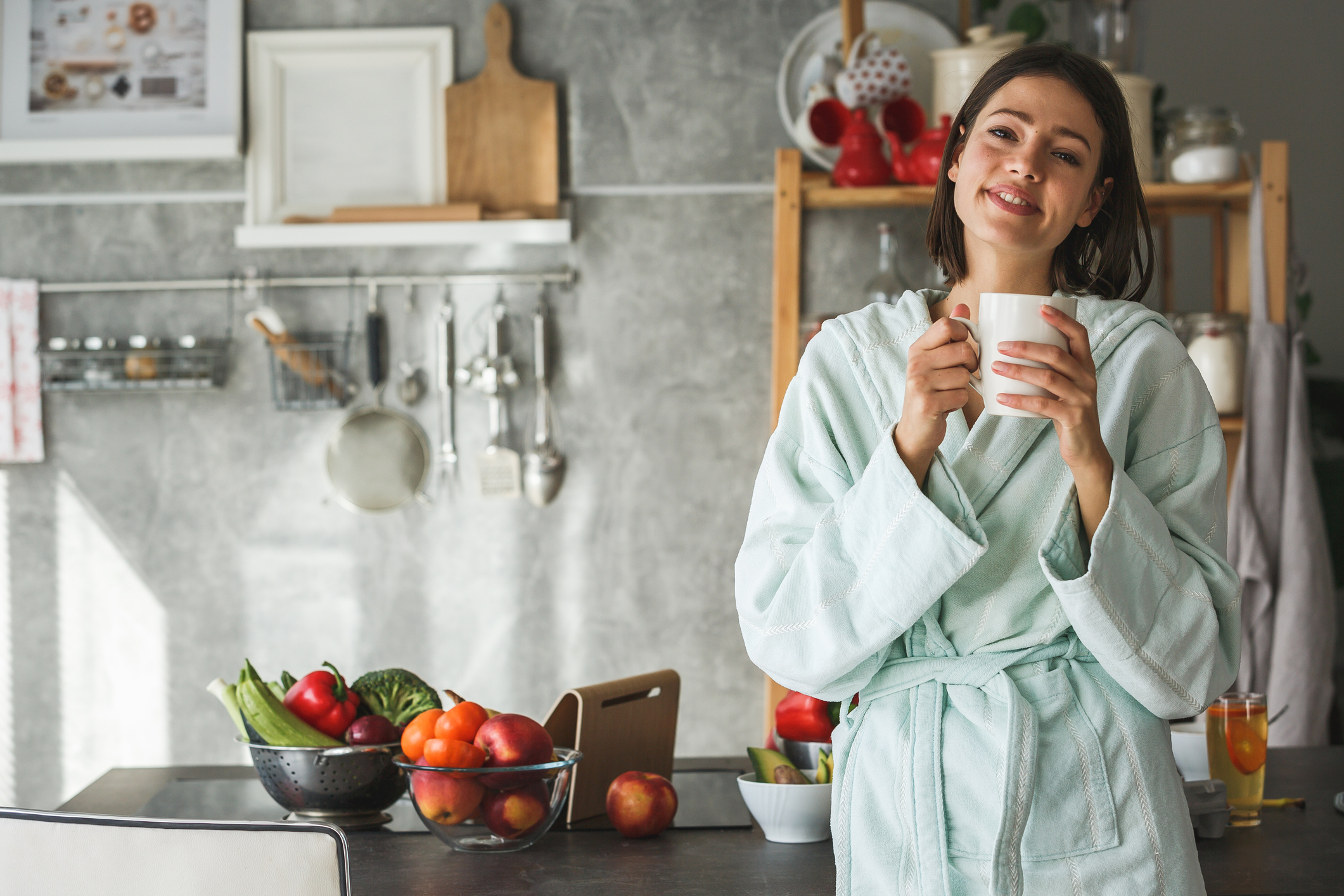 Copy space shot of a smiling woman wearing bathrobe and holding a cup in the kitchen.