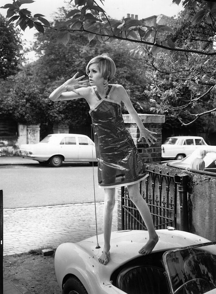 Twiggy modelling a transparent plastic halterneck dress, standing on  the boot of a car.   (Photo by Terry Disney/Getty Images)
