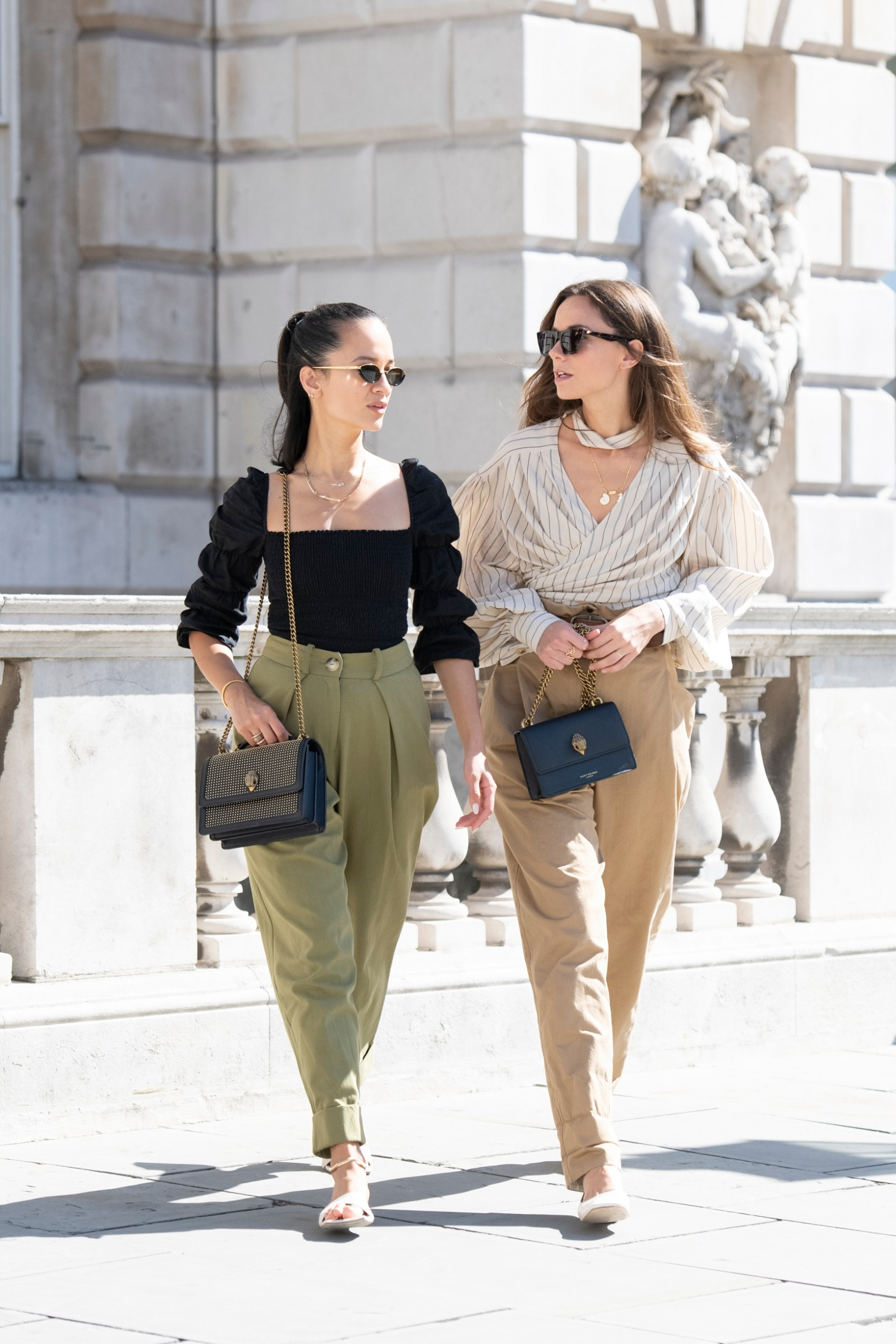 LONDON, ENGLAND - SEPTEMBER 13: Anna Rosa Vitiello wears a Kurt Geiger bag, Reformation top, Maxine shoes, Topshop trousers and Linda Farrow sunglasses with Florrie Thomas wearing Aeyde shoes, Kurt Geiger bag, Rag and Bone sunglasses, Flow belt, trousers and shirt on September 13, 2019 in London, England. (Photo by Kirstin Sinclair/Getty Images for Kurt Geiger)