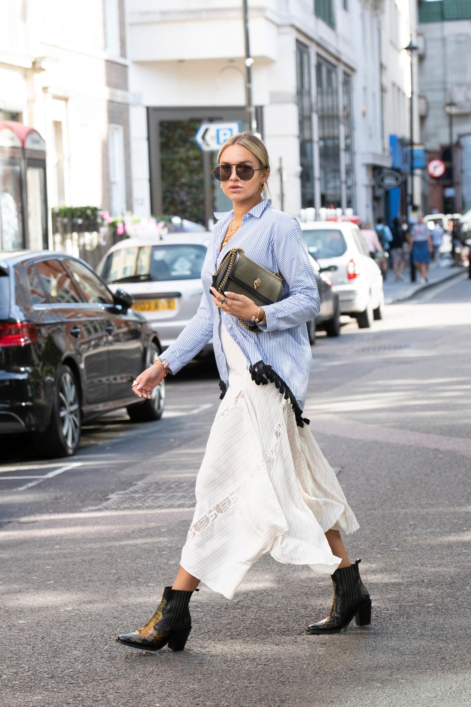 LONDON, ENGLAND - SEPTEMBER 15: Nina Suess wears a Zara shirt, Givenchy sunglasses, Chloe skirt, Kurt Geiger boots and bag on September 15, 2019 in London, England. (Photo by Kirstin Sinclair/Getty Images for Kurt Geiger)