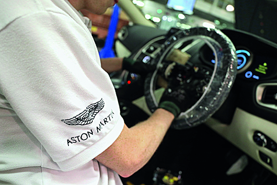 An employee fits the steering wheel in to an Aston Martin DB11 luxury automobile on the final assembly line at Aston Martin Lagonda Ltd.'s manufacturing and assembly plant in Gaydon, U.K., on Tuesday, June 6, 2017. Aston Martinmay consider an initial public offering as early as next year as the British maker of James Bonds cars seeks to capitalize on the success of Ferrari NVs listing to lure investors, people familiar with the matter said. Photographer: Chris Ratcliffe/Bloomberg via Getty Images