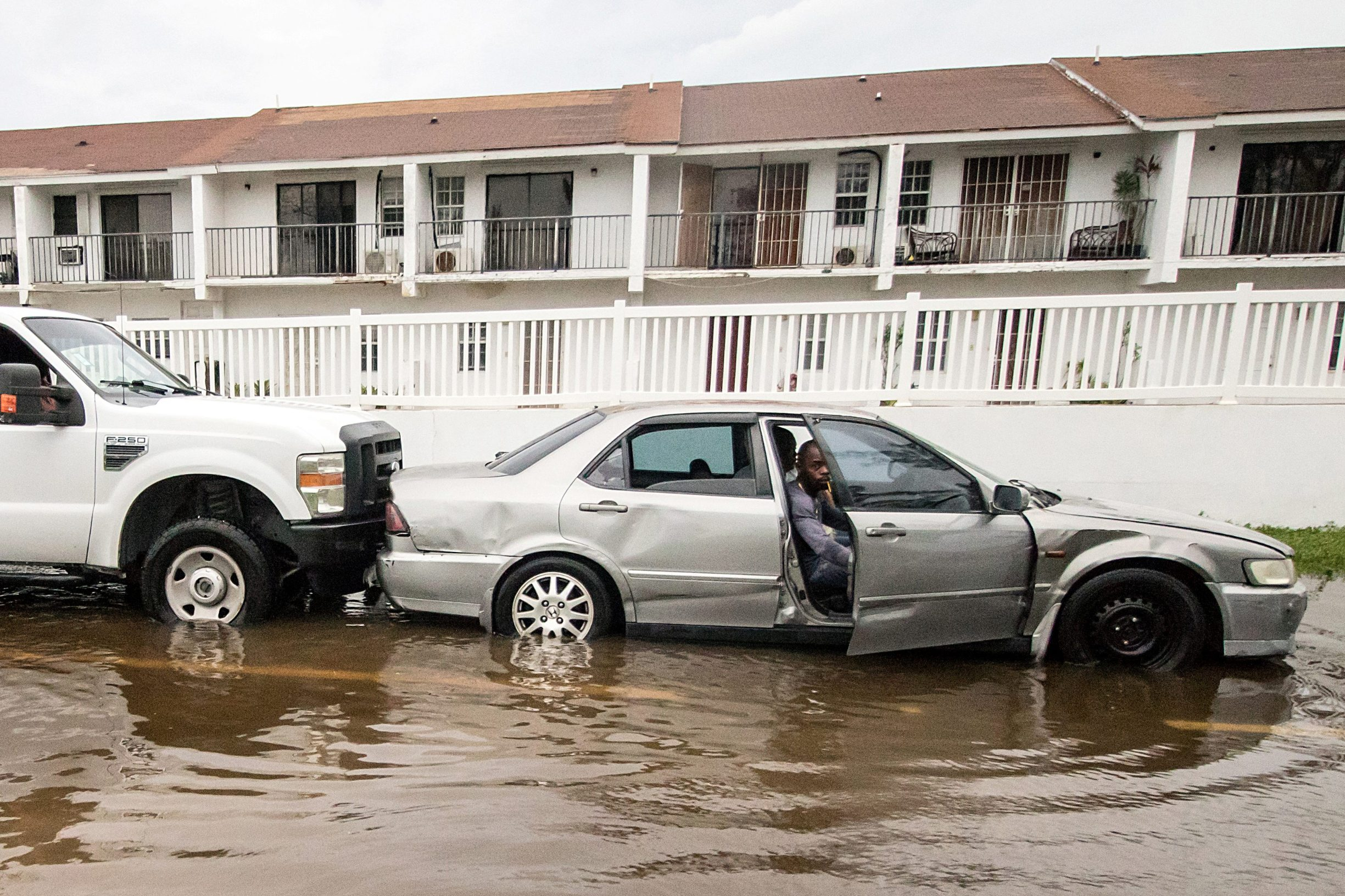 A man driving a stalled car is pushed by a truck through a flooded street after the effects of Hurricane Dorian arrived in Nassau, Bahamas September 2, 2019. REUTERS/John Marc Nutt MANDATORY CREDIT. NO RESALES. NO ARCHIVES