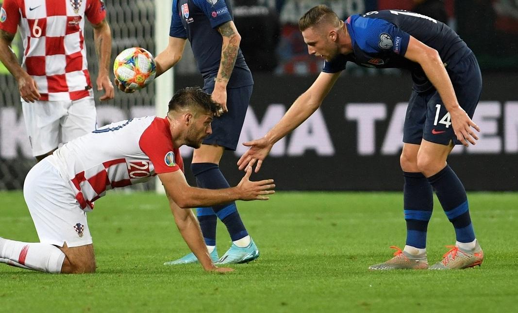 Soccer Football - Euro 2020 Qualifier - Group E - Slovakia v Croatia - City Arena, Trnava, Slovakia - September 6, 2019  Croatia's Bruno Petkovic is helped up by Slovakia's Milan Skriniar      REUTERS/Radovan Stoklasa - RC1E3C1B4820