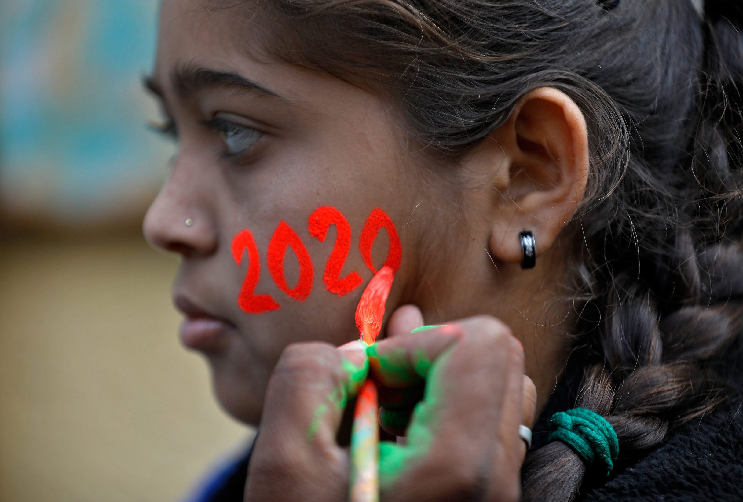 A girl gets her face painted in the digits of number 2020 during celebrations to welcome the New Year at a school in Ahmedabad, India, December 31, 2019. REUTERS/Amit Dave