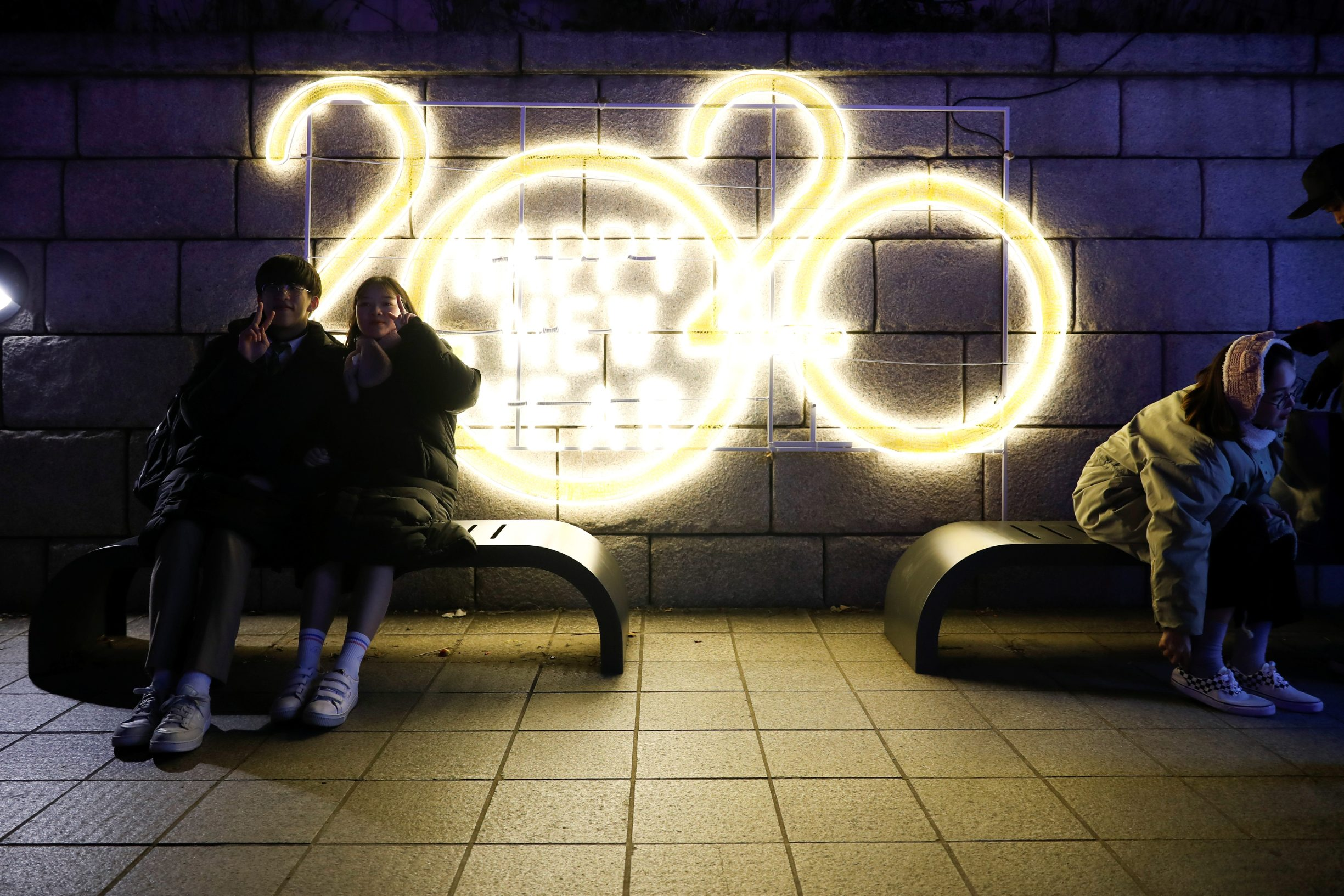 A couple poses for a picture in front of a 2020 luminous sign during New YearÄôs Eve in Seoul, South Korea December 31, 2019. REUTERS/Kim Hong-Ji