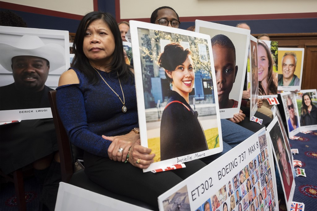 People hold up pictures of the victims of Boeing 737 MAX accidents as Federal Aviation Administration Administrator Stephen Dickson testifies before the House Committee on Transportation and Infrastructure on Capitol Hill in Washington, DC, on December 11, 2019. (Photo by JIM WATSON / AFP)