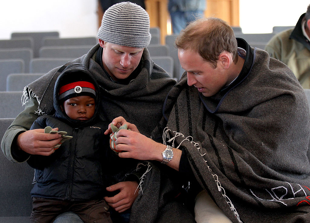 SEMONKONG, LESOTHO - JUNE 17:  Prince Harry and Prince William put gloves on a young boy during a visit to a child education centre on June 17, 2010 in Semonkong, Lesotho. The two Princes are on a joint trip to Africa which takes in Botswana, Lesotho and finally South Africa. During that time they will visit a number of projects supported by their respective charities Sentebale (Prince Harry) and Tusk Trust (Prince William). The trip will culminate with the brothers watching the England vs Algeria World Cup match in Cape Town.  (Photo by Chris Jackson/Getty Images)