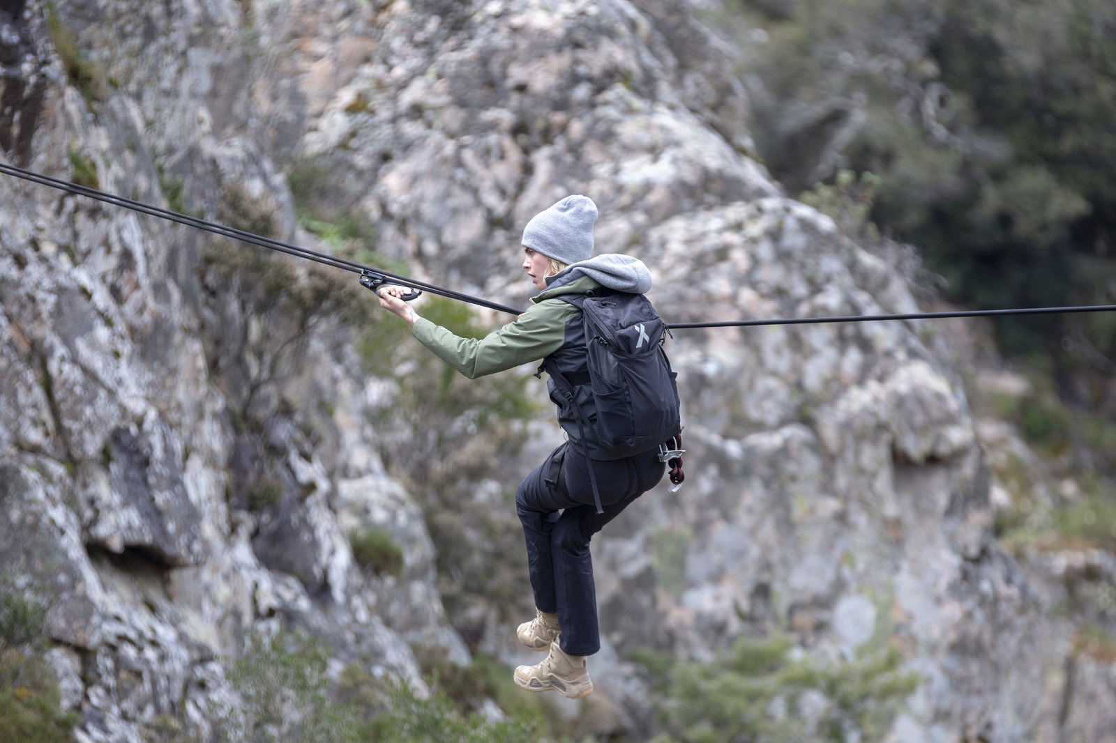 Sardinia, Italy - Cara Delevingne pulls herself across a static line high above a gorge for National Geographic's RUNNING WILD WITH BEAR GRYLLS. (National Geographic/Jeff Ellingson)