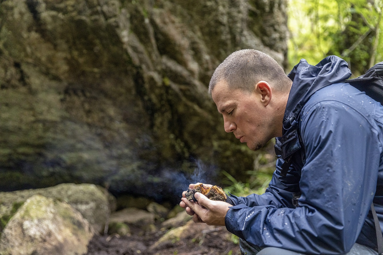 Norway - Channing Tatum gently blows on a Chaga mushroom to keep an ember glowing for National Geographic's RUNNING WILD WITH BEAR GRYLLS. (National Geographic/Ben Simms)