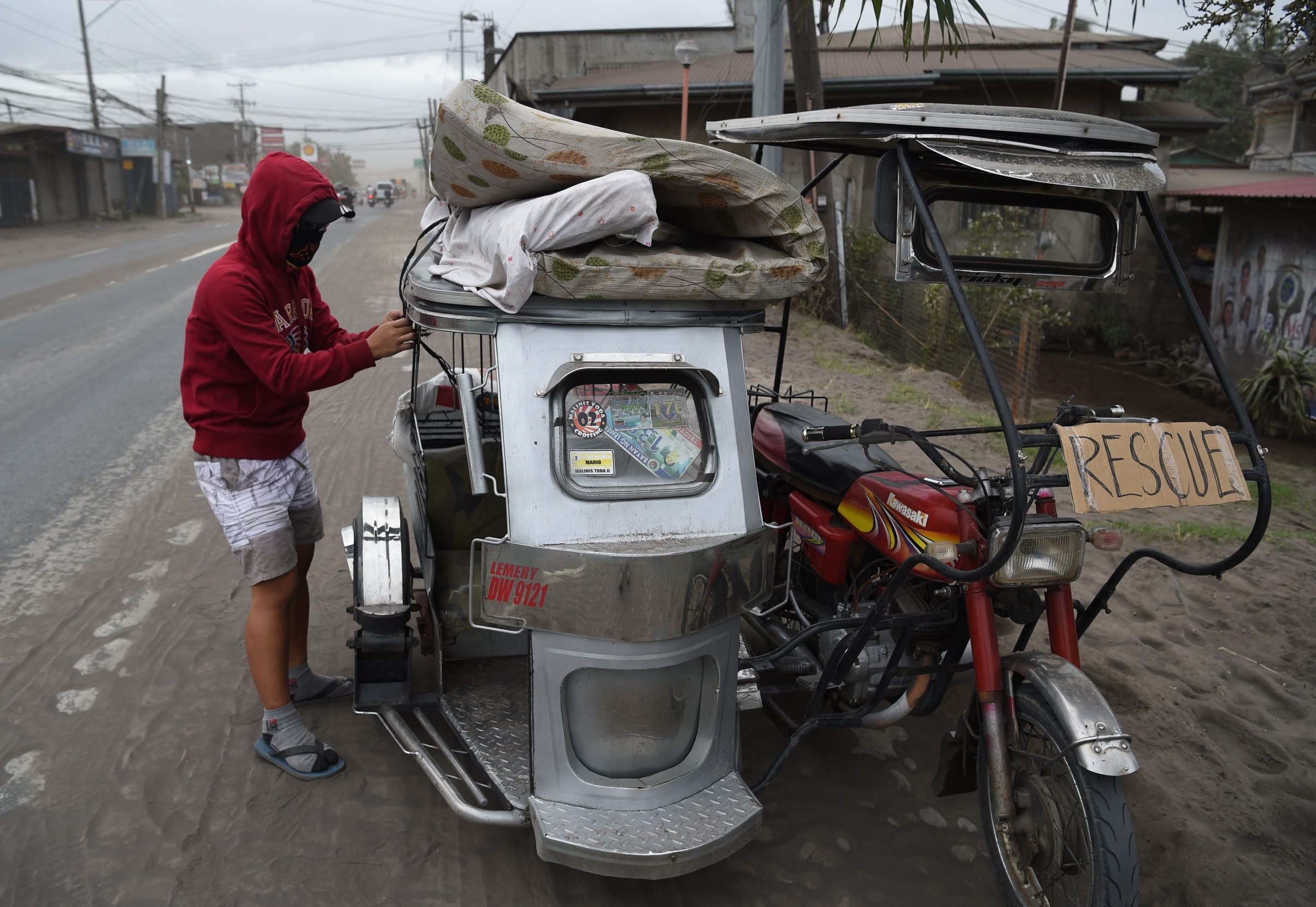 A volcano-affected resident loads his belongings onto a tricycle while evacuating Lemery town, Batangas province south of Manila on January 15, 2020. - Philippine authorities were struggling January 15 to keep thousands of evacuees from returning to homes in areas threatened by a feared massive eruption of Taal volcano. (Photo by Ted ALJIBE / AFP)