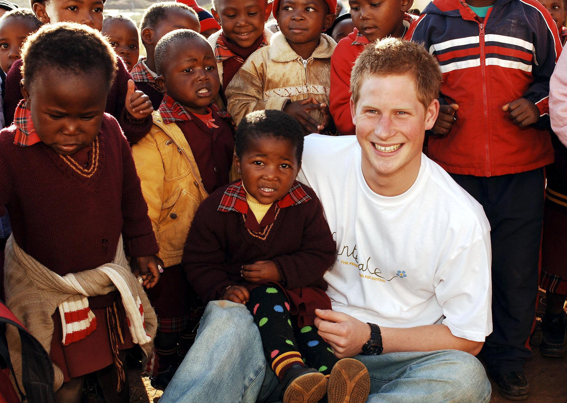 Prince Harry wears a shirt with the Sentebale logo as he holds a small girl while on visit to the Good Shepherd home, on a return visit to Lesotho. The Prince was in the country to launch his new charity called 'Sentebale', which means 'Forget me not', to benefit children orphaned by AIDS PRINCE HARRY IN LESOTHO TO LAUNCH A NEW CHARITY CALLED 'SENTEBALE', LESOTHO - 24 APR 2006, Image: 223734840, License: Rights-managed, Restrictions: NOT UK UNTIL 26 MAY 2006, Model Release: no, Credit line: REX / Shutterstock Editorial / Profimedia