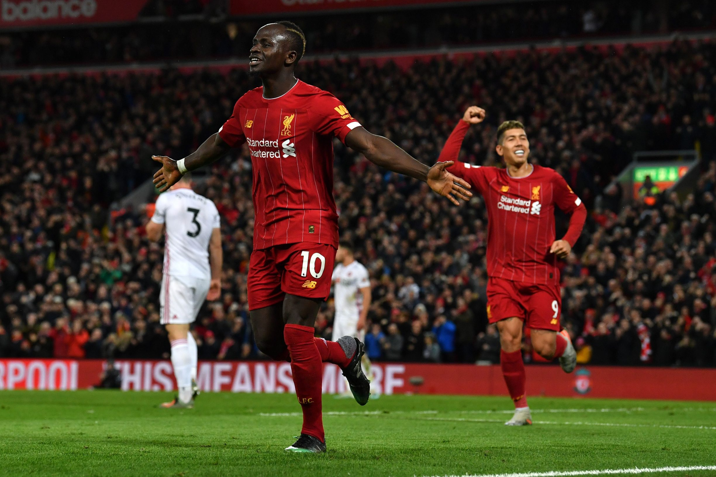 Liverpool's Senegalese striker Sadio Mane (L) celebrates with Liverpool's Brazilian midfielder Roberto Firmino after he scores his team's second goal during the English Premier League football match between Liverpool and Sheffield United at Anfield in Liverpool, north west England on January 2, 2020. (Photo by Paul ELLIS / AFP) / RESTRICTED TO EDITORIAL USE. No use with unauthorized audio, video, data, fixture lists, club/league logos or 'live' services. Online in-match use limited to 120 images. An additional 40 images may be used in extra time. No video emulation. Social media in-match use limited to 120 images. An additional 40 images may be used in extra time. No use in betting publications, games or single club/league/player publications. /