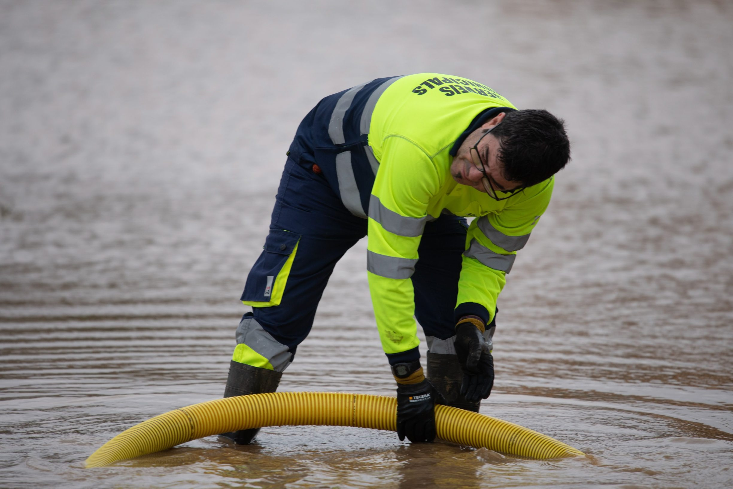 A man drains water on a flooded street in Malgrat de Mar, near Girona on January 22, 2020, as storm Gloria batters Spanish eastern coast. - A winter storm which has killed three people lashed much of eastern Spain for a third day yesterday, cutting power, forcing the closure of schools and severing road and rail links. National weather agency Aemet placed most of northeastern Spain on alert because of the storm packing gusts of over 100 kilometres (60 miles) per hour, heavy snowfall, freezing rain and massive waves which smashed into seafront promenades, damaging shops and restaurants. (Photo by Josep LAGO / AFP)
