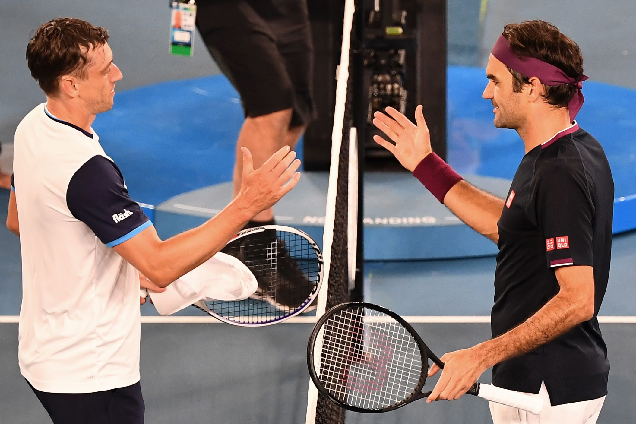Switzerland's Roger Federer (R) prepares to shake hands with Australia's John Millman after his victory during their men's singles match on day five of the Australian Open tennis tournament in Melbourne on January 24, 2020. (Photo by William WEST / AFP) / IMAGE RESTRICTED TO EDITORIAL USE - STRICTLY NO COMMERCIAL USE