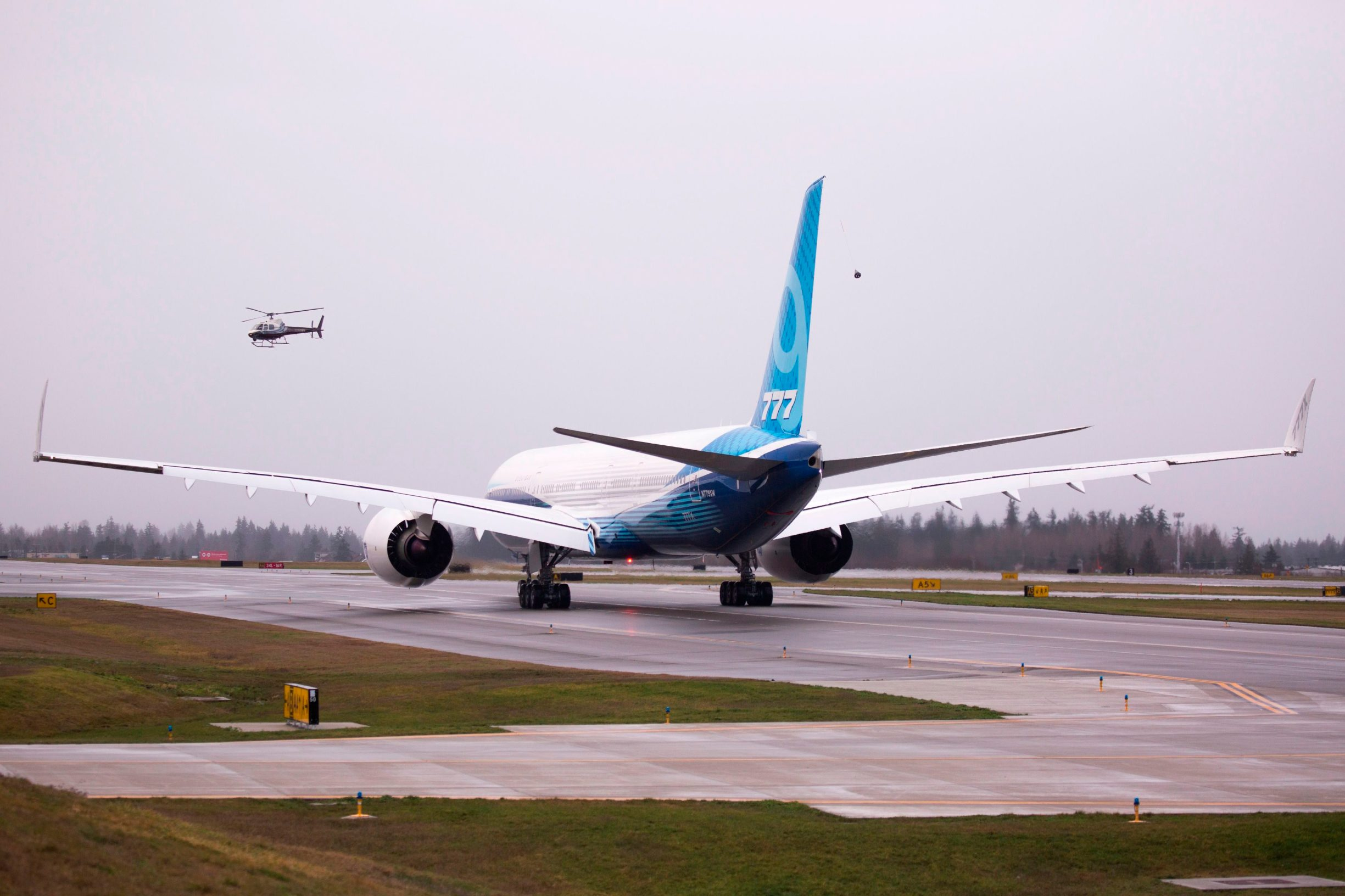 A helicopter follows a Boeing 777X airplane as it taxis before its inaugural flight at Paine Field in Everett, Washington on January 25, 2020. - Boeing's new long-haul 777X airliner made its first flight Saturday, a major step forward for the company whose broader prospects remain clouded by the 737 MAX crisis. The plane took off from a rain-slicked runway a few minutes after 10:00 am local time (1800 GMT), at Paine Field in Everett, Washington, home to Boeing's manufacturing site in the northwestern US. (Photo by Jason Redmond / AFP)