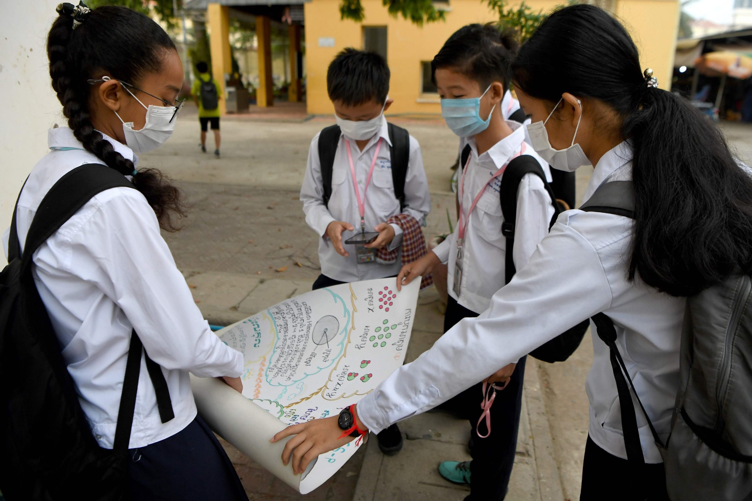 Mask-clad students discuss their homework at a school in Phnom Penh on January 28, 2020. - Cambodia's health ministry reported the country's first case of the deadly coronavirus on January 27. The virus, which can cause a pneumonia-like acute respiratory infection, has in a matter of weeks killed more 106 people and infected more than 4,000 in China, while cases have been identified in more than a dozen other countries. (Photo by TANG CHHIN Sothy / AFP)