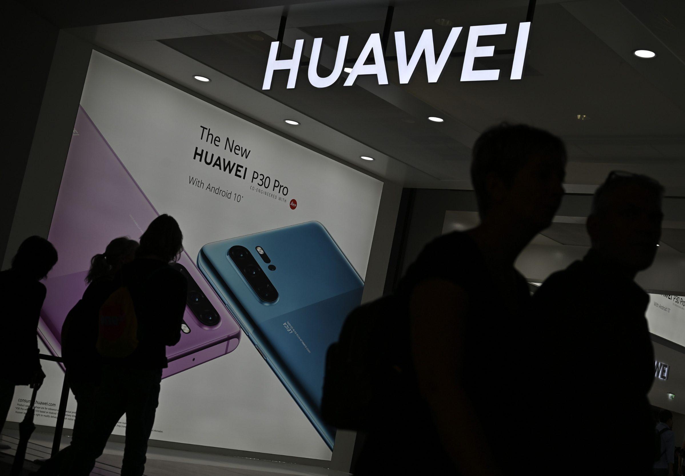Ilustracija: prolaznici ispred promotivnog plakata tvrtke Huawei