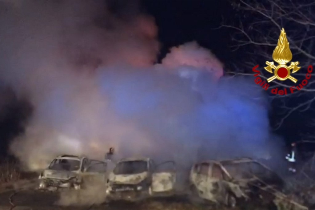 This image grabbed from a video taken and handout on January 29, 2020 by the Italian Department of firefighters, the Vigili del Fuoco, shows rescuers intervening after criminals attempted to ambush an armoured truck on a stretch of highway between Milan and Lodi, in San Zenone al Lambro. - Several burning vehicles on a highway in northern Italy were set up to stop an armored truck carrying cash, but the truck's driver managed to drive through the wall of fire and escape. The attack occurred shortly before midnight late on January 28, 2020, as criminals set fire to about ten vehicles, all probably stolen, in both directions of travel on the motorway. (Photo by Handout / Vigili del Fuoco / AFP) / RESTRICTED TO EDITORIAL USE - MANDATORY CREDIT