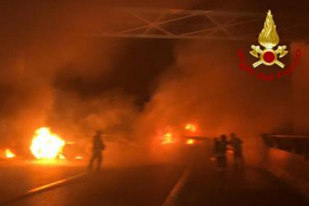 This photo taken and handout on January 29, 2020 by the Italian Department of firefighters, the Vigili del Fuoco, shows rescuers intervening after criminals attempted to ambush an armoured truck on a stretch of highway between Milan and Lodi, in San Zenone al Lambro. - Several burning vehicles on a highway in northern Italy were set up to stop an armored truck carrying cash, but the truck's driver managed to drive through the wall of fire and escape. The attack occurred shortly before midnight late on January 28, 2020, as criminals set fire to about ten vehicles, all probably stolen, in both directions of travel on the motorway. (Photo by Handout / various sources / AFP) / RESTRICTED TO EDITORIAL USE - MANDATORY CREDIT