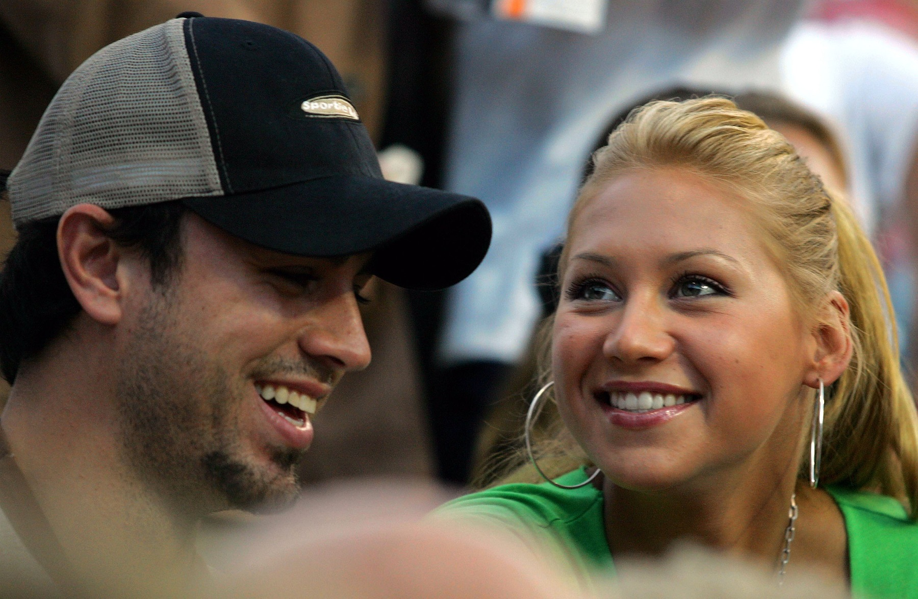 LOS ANGELES - JULY 13:  Tennis player Anna Kournikova and singer Enrique Iglesias watch Andre Agassi play against Alex Bogomolov, Jr. during day 2 of the Mercedes-Benz Cup  on July 13, 2004 at the Los Angeles Tennis Center at UCLA in Los Angeles, California.  (Photo by Ronald Martinez/Getty Images)