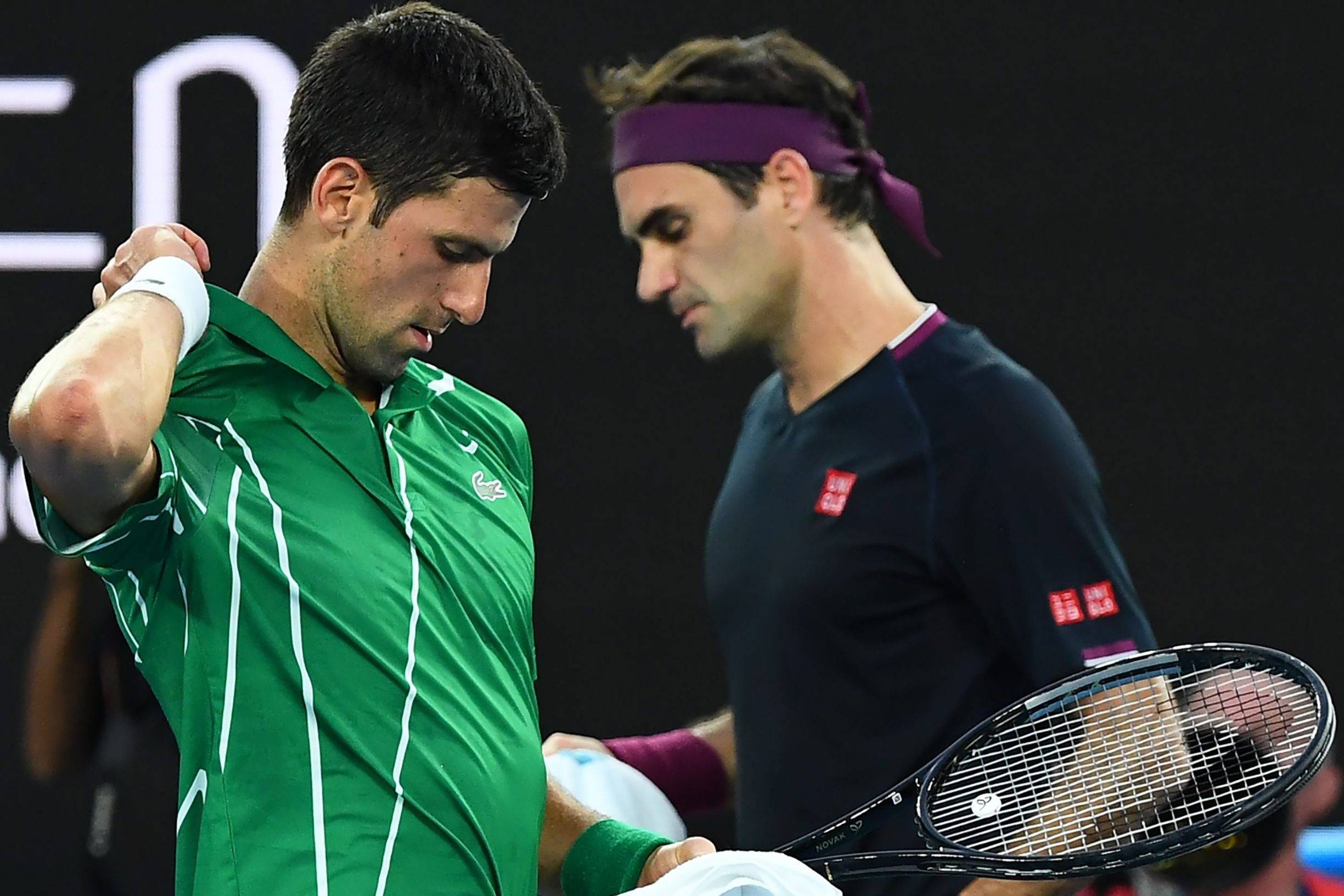 TOPSHOT - Serbia's Novak Djokovic (L) walks past Switzerland's Roger Federer during their men's singles semi-final match on day eleven of the Australian Open tennis tournament in Melbourne on January 30, 2020. (Photo by William WEST / AFP) / IMAGE RESTRICTED TO EDITORIAL USE - STRICTLY NO COMMERCIAL USE