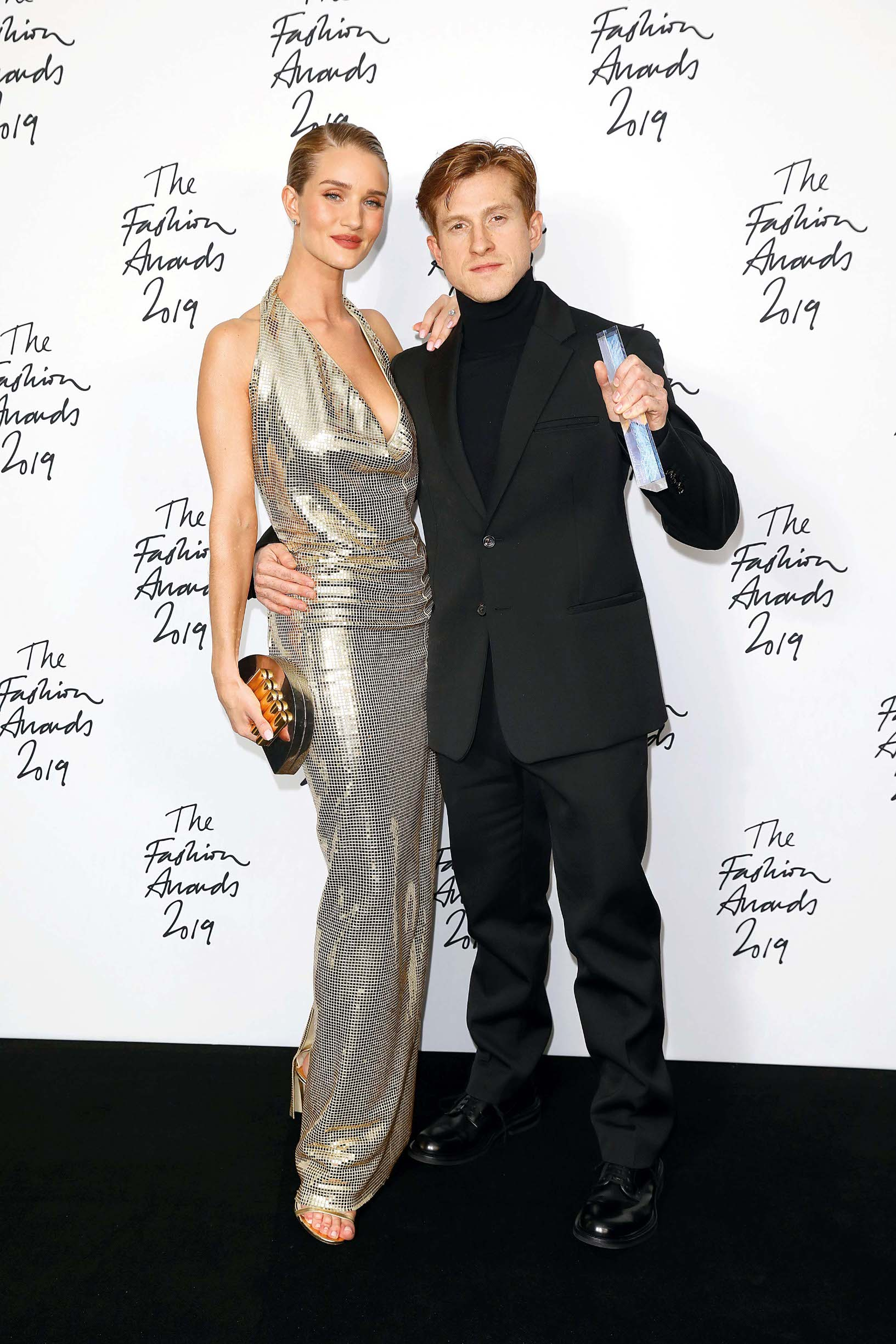 LONDON, ENGLAND - DECEMBER 02:  Daniel Lee poses with Rosie Huntington-Whiteley in the winners room after accepting the Accessories Designer of the Year award on behalf of Bottega Veneta during The Fashion Awards 2019 held at Royal Albert Hall on December 02, 2019 in London, England. (Photo by Tim Whitby/BFC/Getty Images)