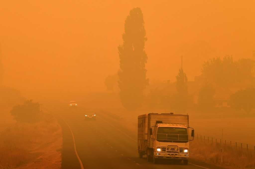 Residents commute on a road through thick smoke from bushfires in Bemboka, in Australia's New South Wales state on January 5, 2020. - Australians on January 5 counted the cost from a day of catastrophic bushfires that caused