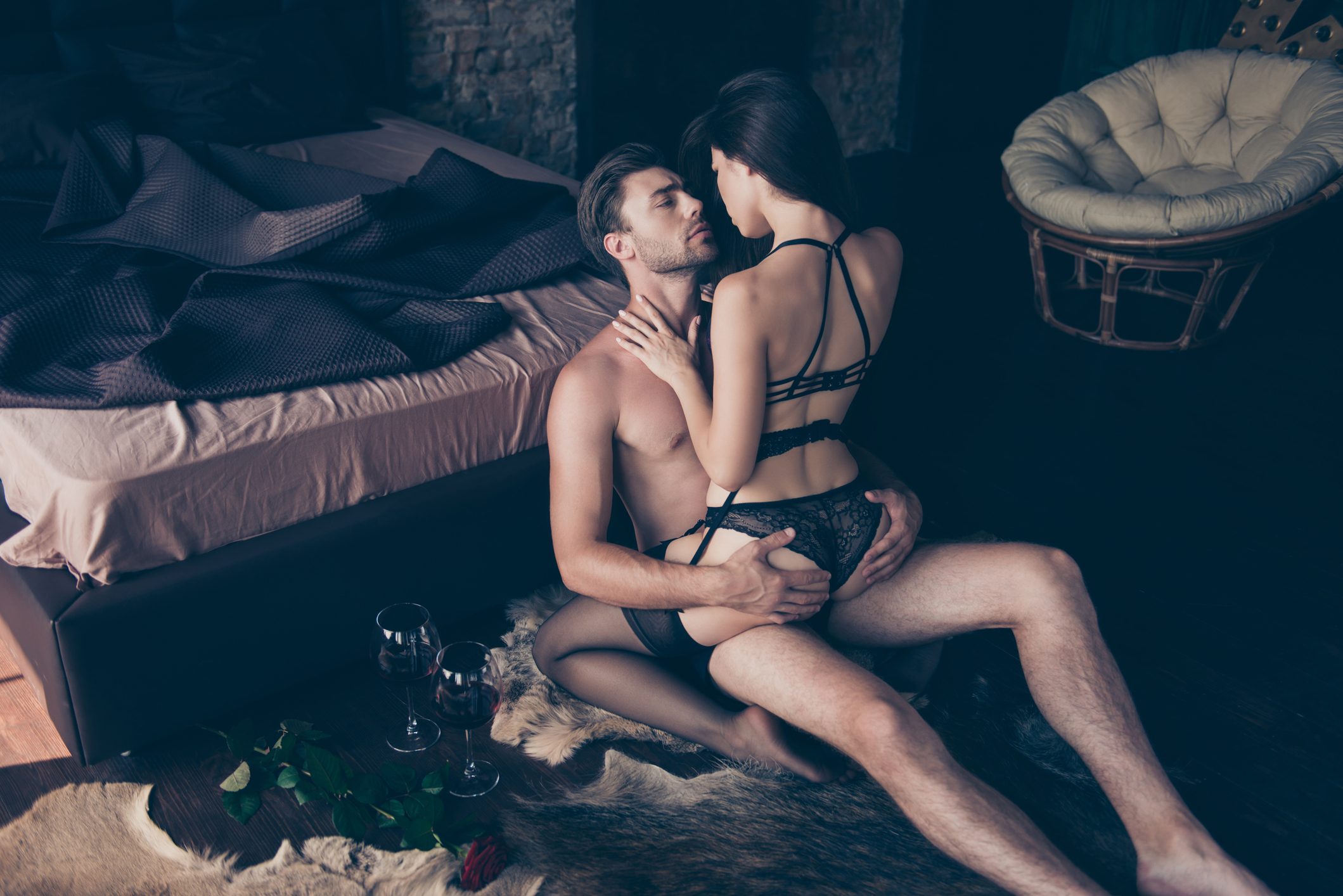 Valentine's day. Rear view of booty hips legs in lace black fashionable underwear set, the masculine hot handsome man is hugging the woman on him, they are sitting on floor in bedroom, dark bedsheet