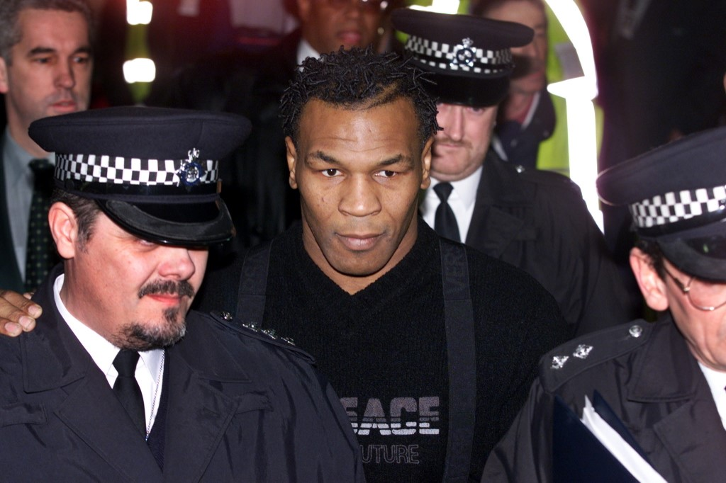 Former world heavyweight champion Mike Tyson (C) is guided through the arrival terminal by police officers as he arrives at Heathrow Airport 16 January 2000 for his controversial fight against Briton Julius Francis. Hundreds of fans and journalists gathered in anticipation of the convicted rapist's arrival at Terminal 4, after a week of doubt over whether he would be allowed into the country.  (ELECTRONIC IMAGE) (Photo by ADRIAN DENNIS / AFP)