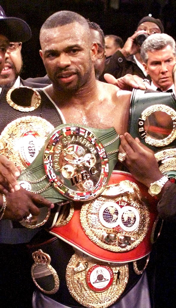 Roy Jones Jr. of the US wears all of his Light Heavyweigh belts after beating compatriot Richard Hall 13 May, 2000 during their Light Heavyweigh title fight at the Conseco Fieldhouse in Indianapolis, IN. Jones won the fight by TKO in the eleventh round.   (ELECTRONIC IMAGE)  AFP PHOTO/JEFF HAYNES (Photo by JEFF HAYNES / AFP)
