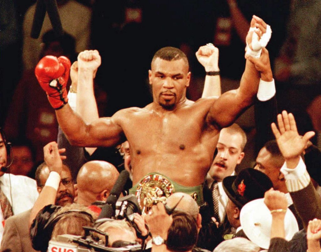 New World Boxing Council (WBC) heavyweight champion Mike Tyson is lifted into the air wearing the championship belt after defeating WBC heavyweight champion Frank Bruno of Great Britain with a third round technical knockout 16 March at the MGM Grand Garden in Las Vegas.     AFP PHOTO/Mike NELSON (Photo by MIKE NELSON / AFP)
