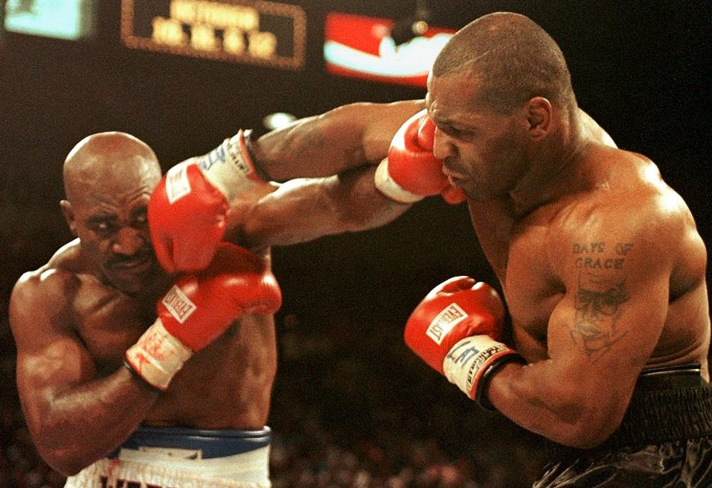 Evander Holyfield (L) and Mike Tyson (R) trade punches 28 June in their WBA heavyweight Cchampionship fight at the MGM Grand Garden Arena in Las Vegas, NV. Holyfield won by disqualification in the the third round after Tyson bit his ear.      AFP PHOTO/JEFF HAYNES (Photo by JEFF HAYNES / AFP)