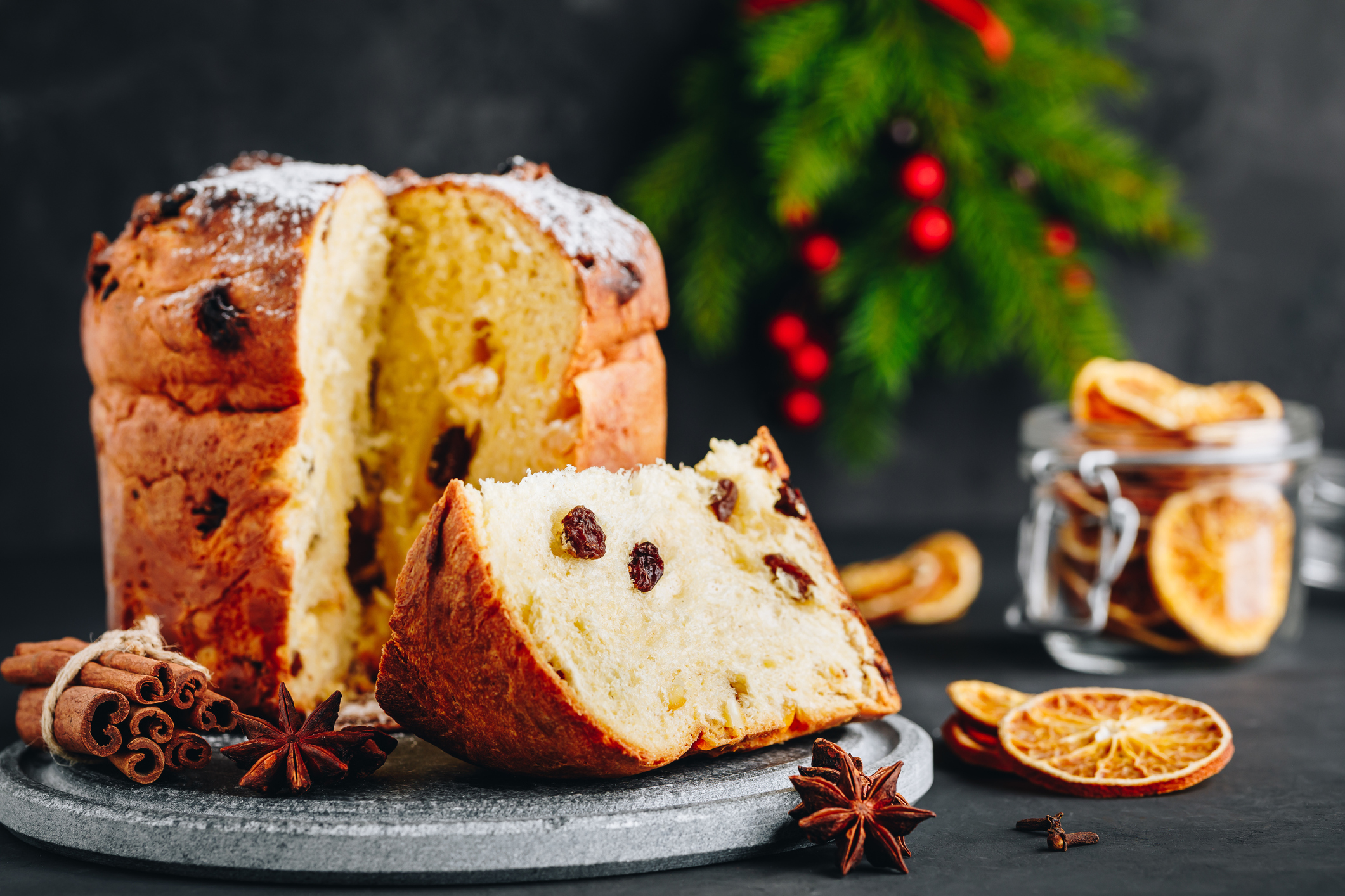Traditional Christmas Panettone cake with dried fruits on dark stone background, copy space.