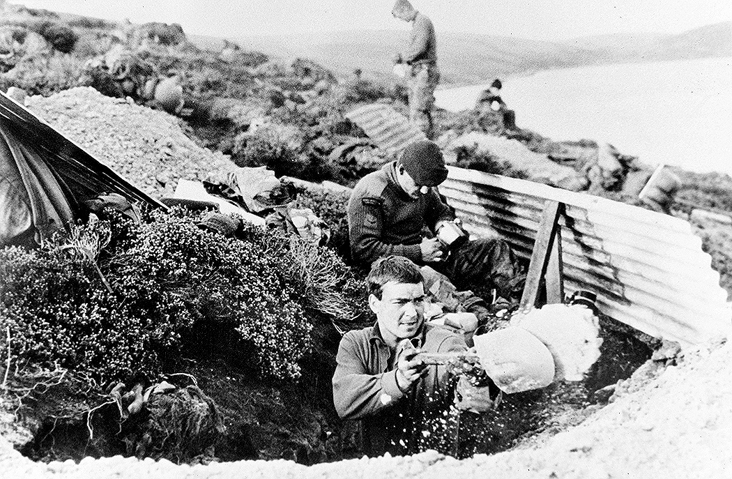 Photograph of British troops, possibly Royal Marine Commandos, digging out a dugout overlooking a body of water, Falklands, 1982. One of fourteen copy photographs of British Army, Royal Navy and Royal Air Force operations in South Atlantic and on the Falkland Islands, 1982. Associated with South Atlantic (Falklands War) (1982)., Image: 328582107, License: Rights-managed, Restrictions: , Model Release: no, Credit line: - / Mary Evans Picture Librar / Profimedia