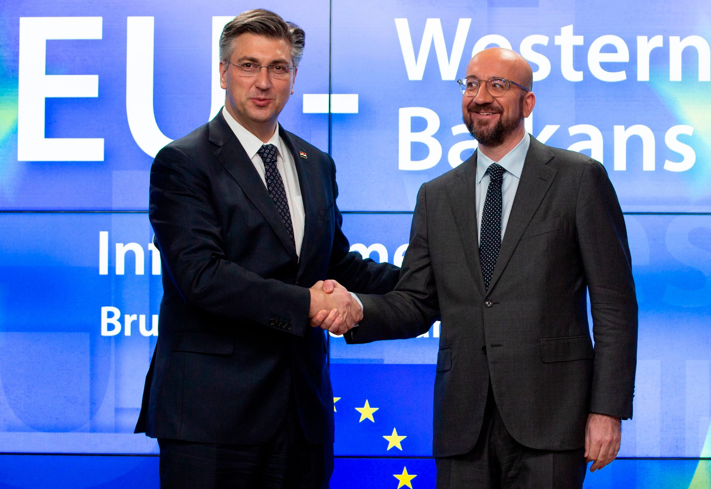 Croatian Prime Minister Andrej Plenkovic (L) is greeted by European Council President Charles Michel as he arrives for an EU-Western Balkans Summit at the EU headquarters in Brussels on February 16, 2020. (Photo by Virginia Mayo / POOL / AFP)