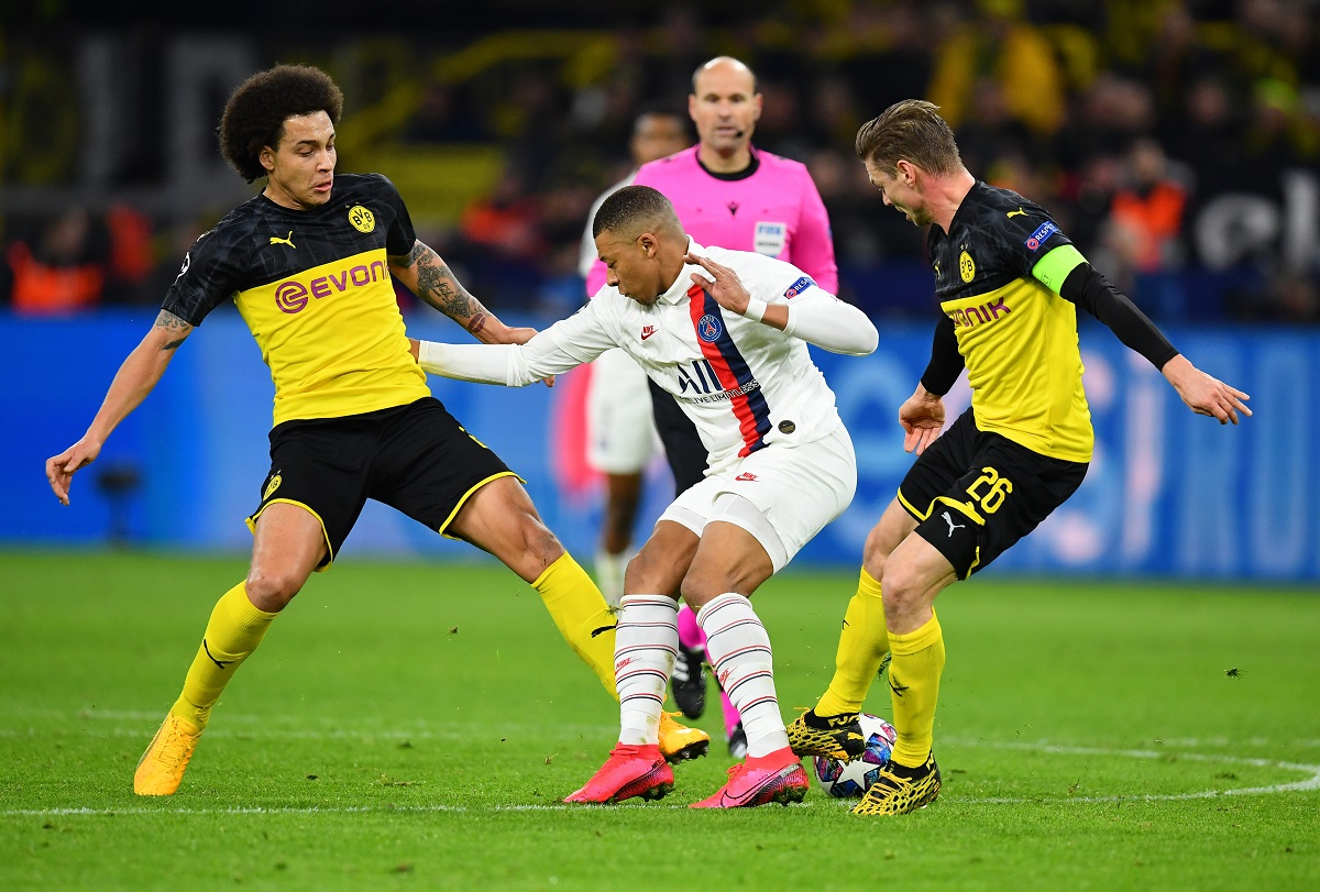 DORTMUND, GERMANY - FEBRUARY 18: Kylian Mbappe of Paris Saint-Germain is challenged by Axel Witsel (L) and Lukasz Piszczek of Borussia Dortmund (R) during the UEFA Champions League round of 16 first leg match between Borussia Dortmund and Paris Saint-Germain at Signal Iduna Park on February 18, 2020 in Dortmund, Germany. (Photo by Stuart Franklin/Bongarts/Getty Images)