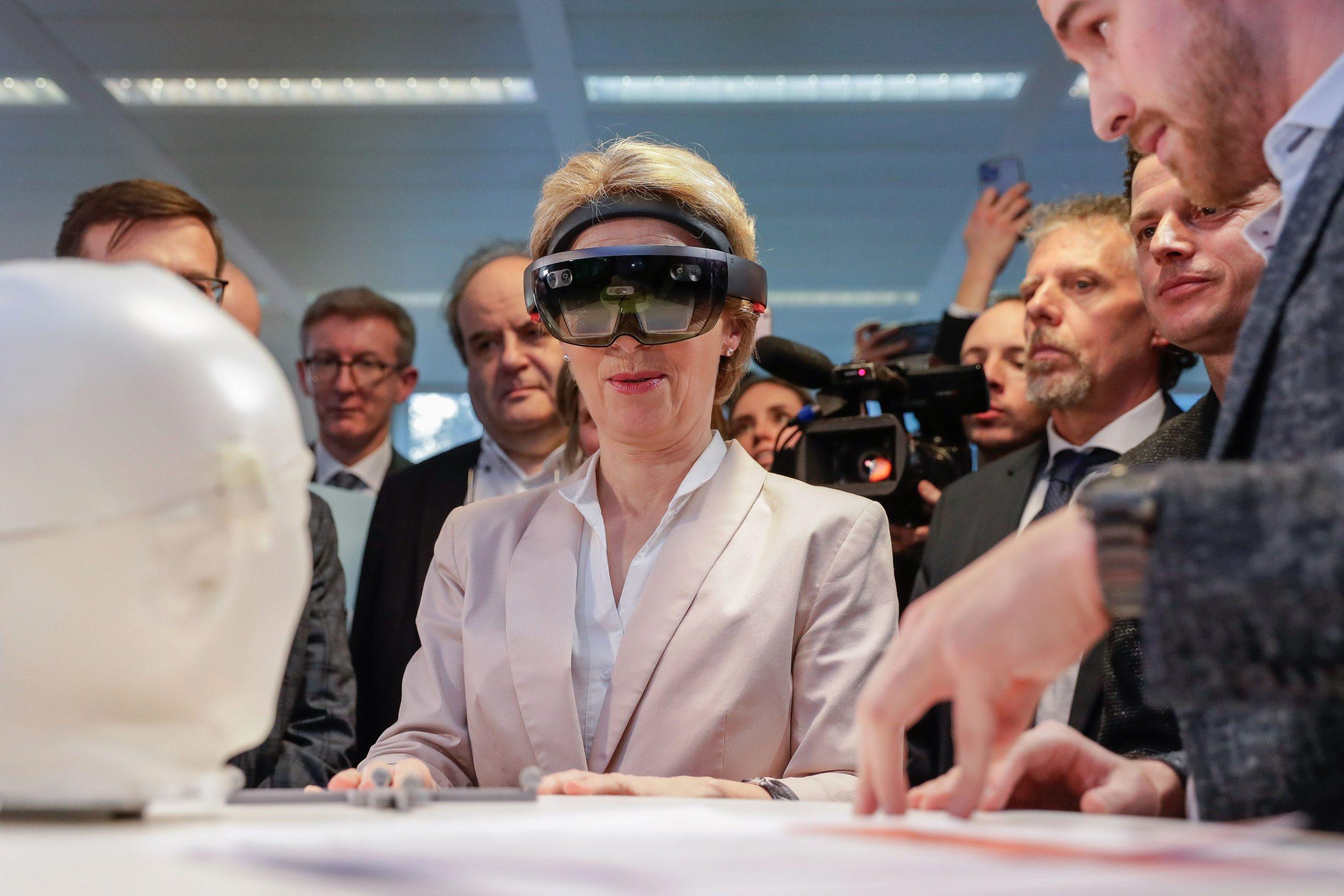 President of the European Commission Ursula von der Leyen (C) looks at the invention