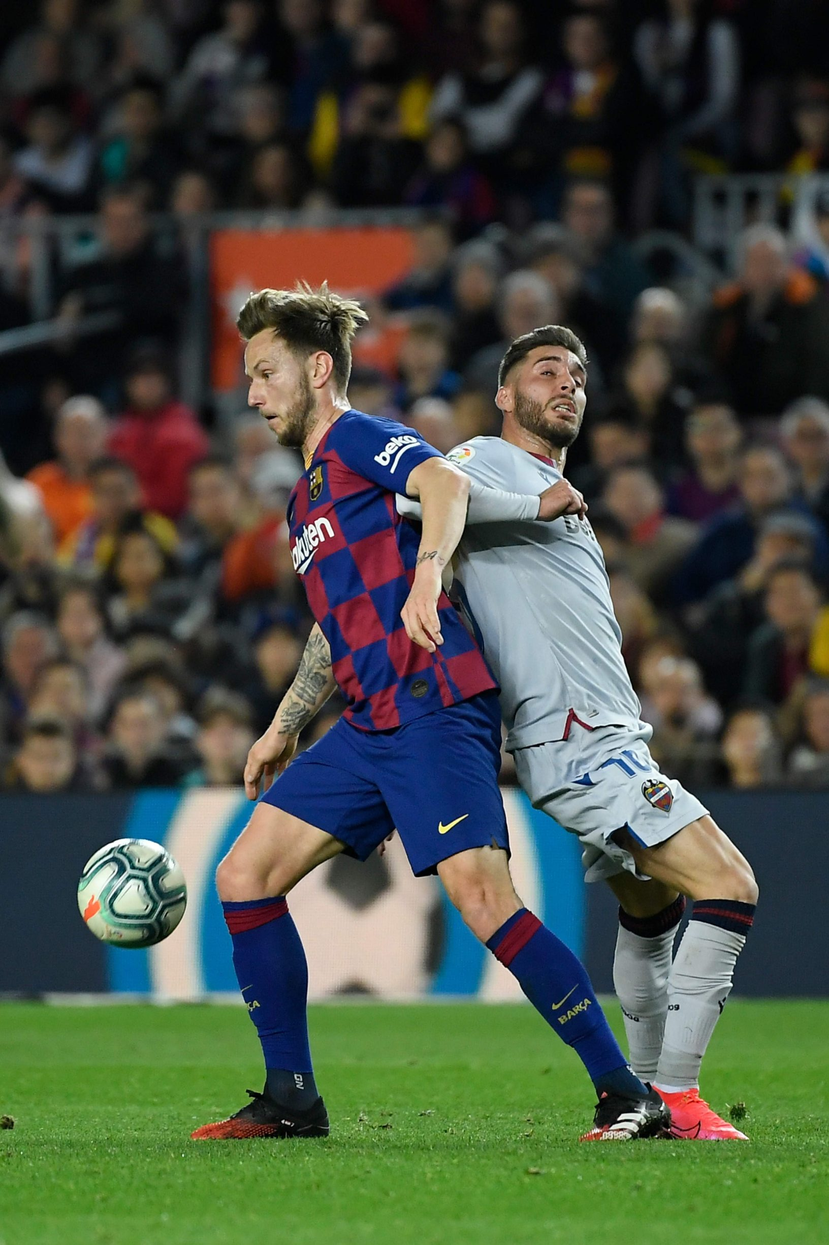 Barcelona's Croatian midfielder Ivan Rakitic (L) challenges Levante's Spanish forward Ruben Rochina during the Spanish league football match be tween FC Barcelona and Levante UD at the Camp Nou stadium in Barcelona, on February 2, 2020. (Photo by LLUIS GENE / AFP)