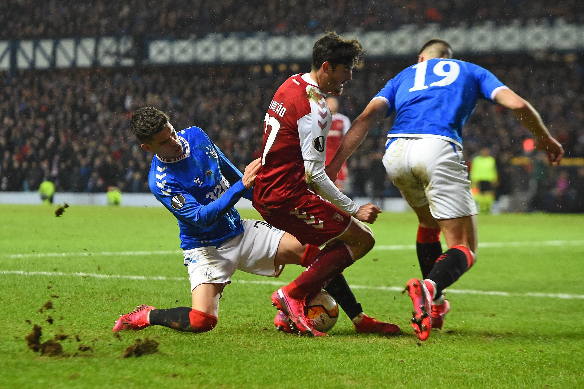 Rangers' Romanian midfielder Ianis Hagi (L) tackles Sporting Braga's Portuguese striker Trincao (C) during the UEFA Europa League round of 32 first leg football match between Rangers and Sporting Braga at the Ibrox Stadium in Glasgow on February 20, 2020. (Photo by ANDY BUCHANAN / AFP)