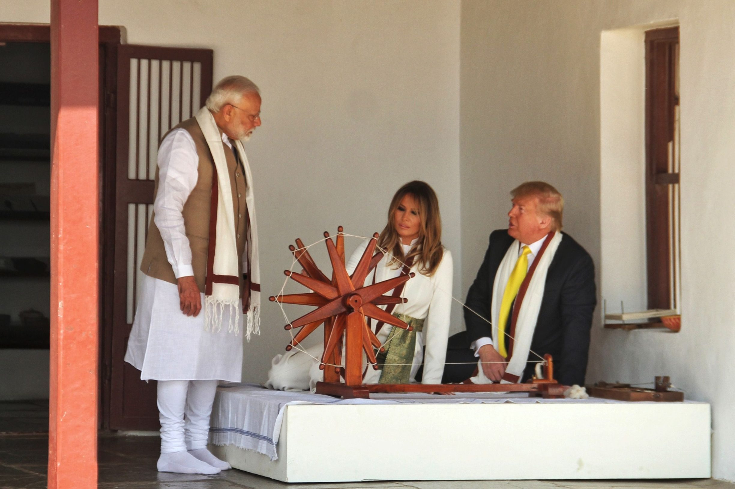 In this handout photograph taken and released by India's Ministry of External Affairs (MEA) on February 24, 2020, US President Donald Trump and First Lady Melania Trump listen to India's Prime Minister Narendra Modi (L) as they sit next to a charkha, or spinning wheel, during their visit at Gandhi Ashram in Ahmedabad. (Photo by - / Indian Ministry of External Affairs (MEA) / AFP) / RESTRICTED TO EDITORIAL USE - MANDATORY CREDIT