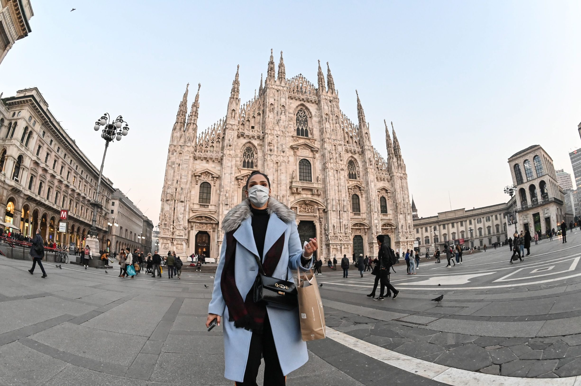 A woman with a protective facemask walks across the Piazza del Duomo, in front of the Duomo, in central Milan, on February 24, 2020, following security measures taken in northern Italy against the COVID-19 the novel coronavirus. - Italy reported on February 24, 2020 its fourth death from the new coronavirus, an 84-year old man in the northern Lombardy region, as the number of people contracting the virus continued to mount. (Photo by Andreas SOLARO / AFP)