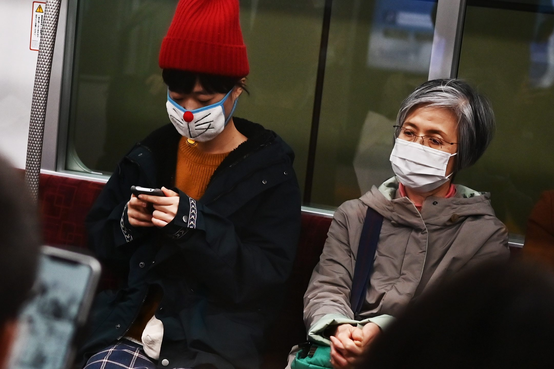 People wearing face masks travel on a train in Tokyo on February 25, 2020. - Japan has more than 150 cases of the COVID-19 coronavirus and five have died. Four of those deaths were passengers who had been on the cruise ship Diamond Princess, quarantined off in Yokohama, where the number of infections is over 690. (Photo by CHARLY TRIBALLEAU / AFP)