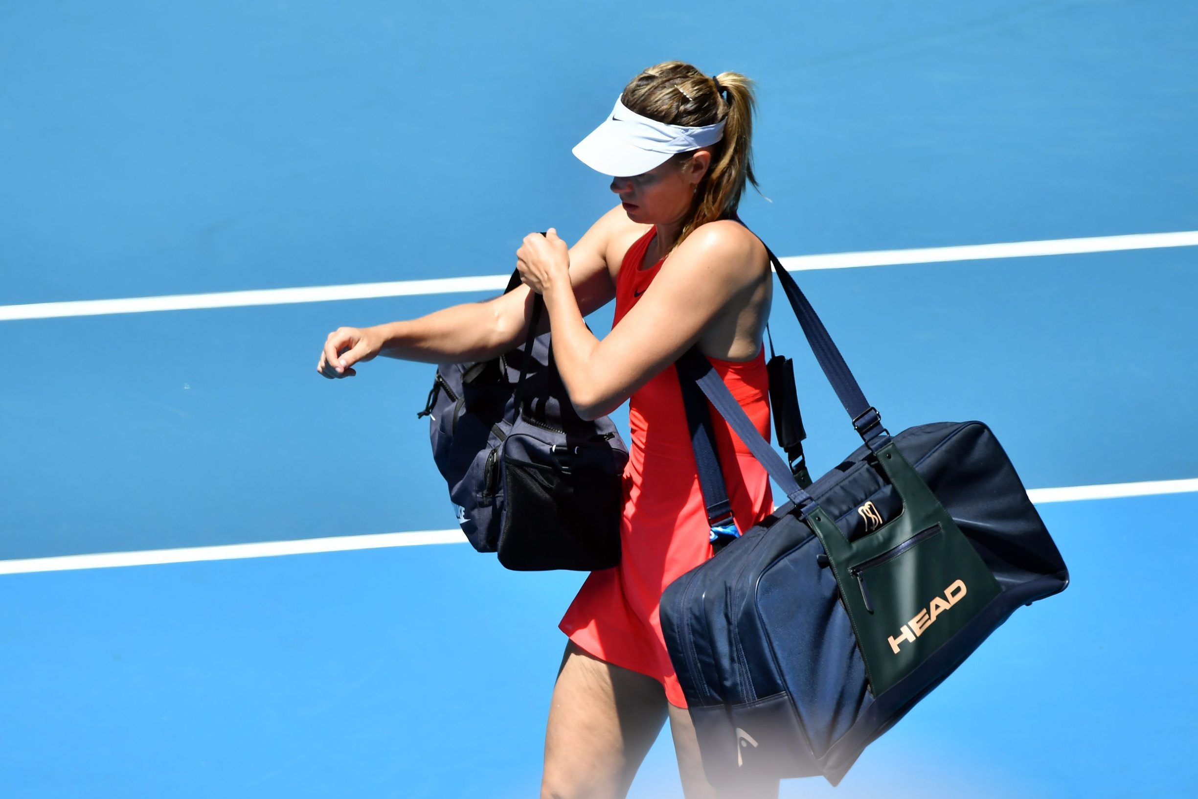Russia's Maria Sharapova (R) leaves after her defeat against Croatia's Donna Vekic during their women's singles match on day two of the Australian Open tennis tournament in Melbourne on January 21, 2020 (Photo by John DONEGAN / AFP) / IMAGE RESTRICTED TO EDITORIAL USE - STRICTLY NO COMMERCIAL USE