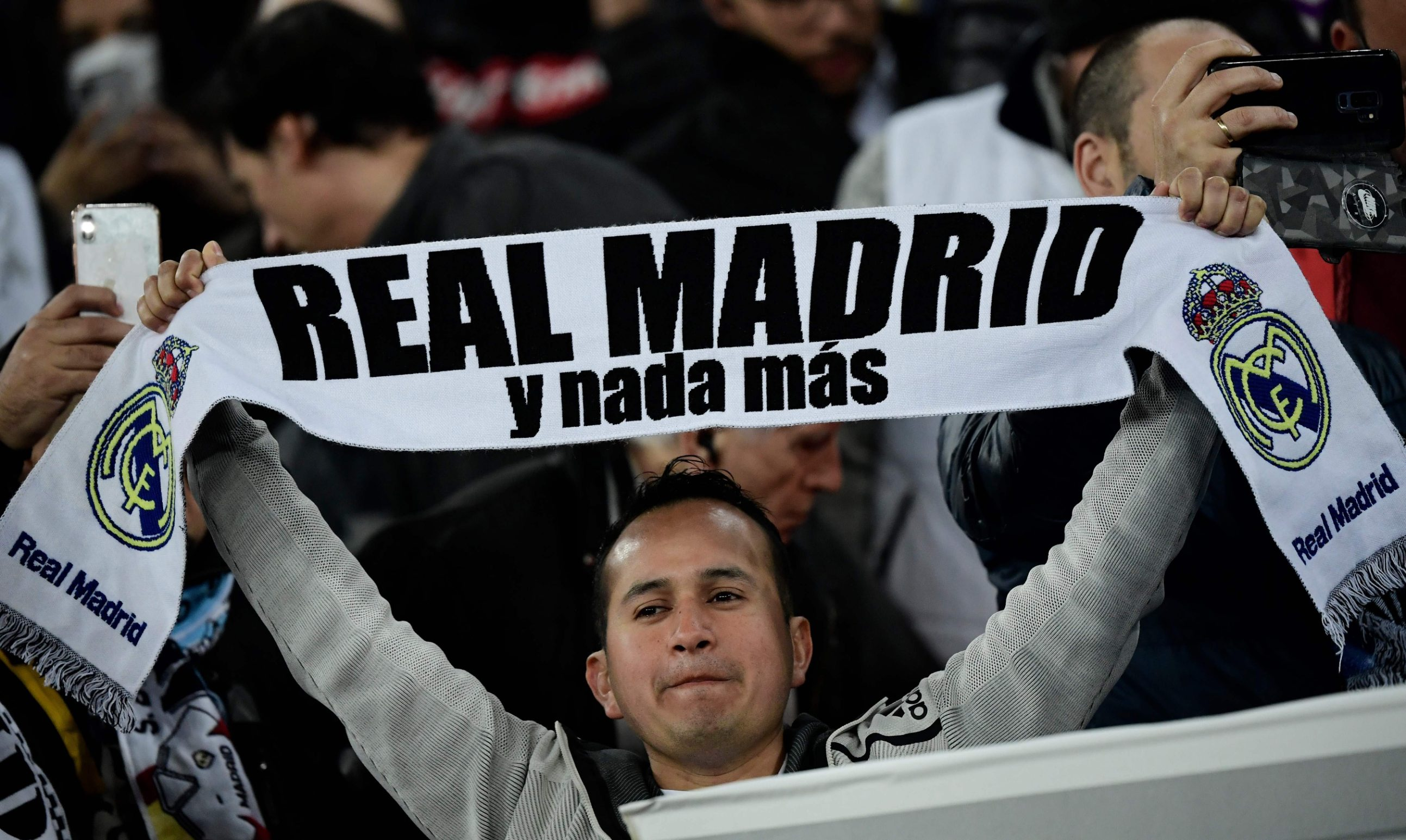 A Real Madrid fan holds up a scarf during the UEFA Champions League round of 16 first-leg football match between Real Madrid CF and Manchester City at the Santiago Bernabeu stadium in Madrid on February 26, 2020. (Photo by JAVIER SORIANO / AFP)